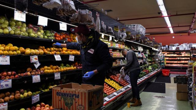 Store employee Luis Gabriel stocks produce at a Pioneer Supermarket in the Bronx on March 25, 2020. (Desiree Rios/The New York Times)