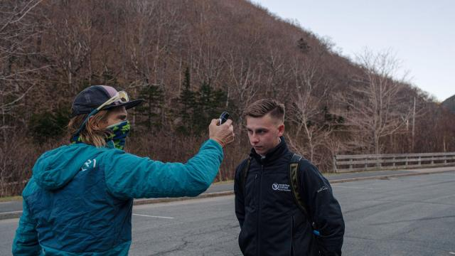Kel Rossiter, left, owner and lead guide of Adventure Spirit, checks the temperature of customer Harry Callewaert before climbing the Whitney Gilman Ridge on the side of Cannon Mountain near Franconia, N.H., Wednesday, May 20, 2020. The U.S. has crossed an uneasy threshold, with all 50 states beginning to reopen in some way two months after the coronavirus thrust the country into lockdown. (John Tully/The New York Times)