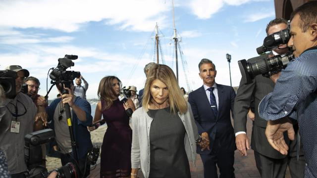 FILE -- Lori Loughlin and her husband, Mossimo Giannulli, leave federal court in Boston, Aug. 27, 2019. Loughlin and her husband, Mossimo Giannulli, a fashion designer, have agreed to plead guilty to charges that they conspired to get their daughters admitted to the University of Southern California as crew recruits, prosecutors announced on Thursday, May 21, 2020, a reversal for the couple after months of maintaining their innocence in the nation's largest-ever admissions prosecution. (Katherine Taylor/The New York Times)