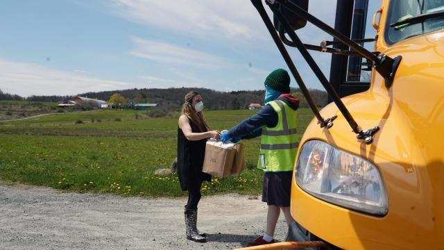 School lunches are delivered by school bus in upstate Kenoza Lake, N.Y., on May 12, 2020. Child hunger is soaring, but two months after Congress approved billions to replace school meals, only 15 percent of eligible children had received benefits. (Michelle V. Agins/The New York Times)