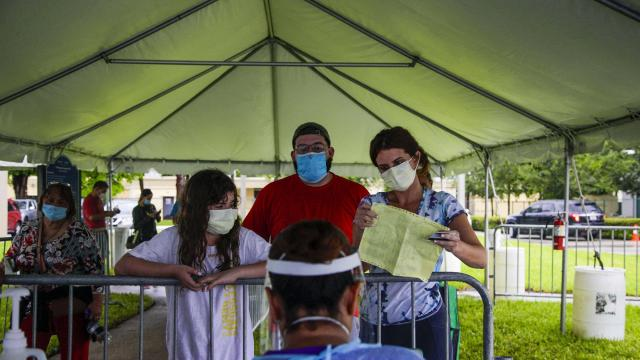 People wait at a coronavirus testing site in Miami, July 22, 2020. President Trump's cancellation of the convention in Florida and sudden embrace of masks may signal his acceptance of a political landscape transformed by the pandemic. (Saul Martinez/The New York Times)