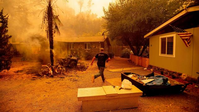 A resident runs into a home to save a dog while flames are getting close as the Hennessey fire continues to rage out of control near Lake Berryessa in Napa, California on August 18, 2020. - As of the late hours of August 18, the Hennessey fire has merged with at least 7 fires and is now called the LNU Lightning Complex fires. Dozens of fires are burning out of control throughout Northern California as fire resources are spread thin. (Photo by JOSH EDELSON / AFP) (Photo by JOSH EDELSON/AFP via Getty Images)