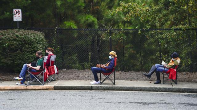 FILE -- Voters wait to enter a polling place to cast their ballots during early voting. Under enormous pressure, many swing states are still trying to shore up a democratic process challenged daily by court cases, new laws and surges in the coronavirus. (Nicole Craine/The New York Times)