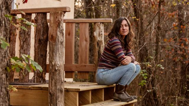 """Danielle Ackley sits on the steps of a cabin she and her husband built for her mother, in Snow Camp, N.C., Nov. 24, 2020. Ackley, a Biden supporter, and her mother have always been different politically. But they agreed to disagree, even after Trump's 2016 win. The arguments have only grown. """"This is not even a political divide, it's a reality divide,"""" Ackley said. (Jeremy M. Lange/The New York Times)"""