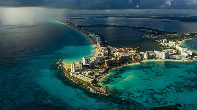 """A rainstorm approaches hotels in Cancún, near Puerto Morelos, Mexico, on Nov. 15, 2020. In an unusual experiment, a coral reef in Mexico is now insured against hurricanes. A team of locals known as """"the Brigade"""" rushed to repair the devastated corals, piece by piece. (Daniel Berehulak/The New York Times)"""