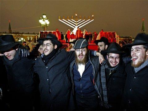 People dance and sing marking the start of Hanukkah in front of the Moscow Kremlin, on Tuesday, Dec. 4, 2007, with Kremlin's Towers in the background. Dozens of people huddled together on Tuesday outside the Kremlin to watch the lighting of a menorah, seen in the background, center. The lighting of a menorah begins an eight-day commemoration of the Jewish uprising in the second century B.C. against the Greek-Syrian kingdom, which had tried to put statues of Greek gods in the Jewish Temple in Jerusalem. (AP Photo/Misha Japaridze)