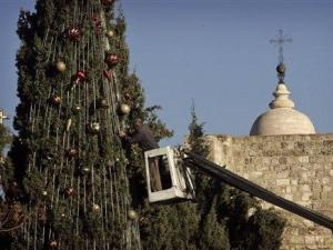 A Palestinian worker uses a crane to fix ornaments onto a Christmas tree next to the Church of the Nativity, believed to be the birthplace of Jesus Christ, in the West Bank town of Bethlehem, Thursday, Dec. 13, 2007. (AP Photo/Sebastian Scheiner)
