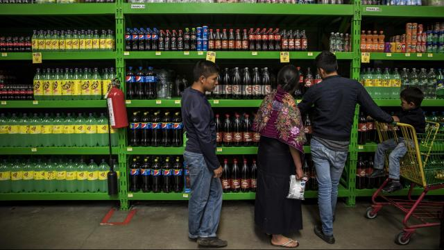 A family shops for soft drinks at Bodega Aurrerá, a discount chain that is owned by Walmart, in San Cristobal de las Casas, Mexico, Oct. 24, 2017. Few predicted when Mexico joined the North American Free Trade Agreement that it would transform the country in a way that would saddle millions with diet-related illnesses. (Adriana Zehbrauskas/The New York Times)