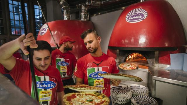 """Pizzas fresh out of the oven at Gino Sorbillo's celebrated pizzeria in Naples, Italy, Dec. 8, 2017. Sorbillo and the city's 3,000 other pizzaiuoli were recently named part of the Intangible Cultural Heritage of Humanity by Unesco. """"It's an art,"""" said Sorbillo. """"It started in Naples and survived the centuries, despite all the difficulties, the earthquakes, Vesuvius, the war, the wars."""" (Gianni Cipriano/The New York Times)"""