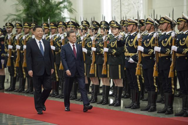 "President Xi Jinping of China, left, and President Moon Jae-in of South Korea at a welcoming ceremony in Beijing, Dec. 14, 2017. After more than a year of frosty relations bordering on hostile, Moon pledged a ""new start"" in his country's dealings with China, a re-engagement that China hopes will lead to stepped-up diplomacy on disarming North Korea. (Nicolas Asfouri/Pool via The New York Times) -- EDITORIAL USE ONLY -- ."