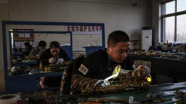 """Factory workers check the seals on saxophones in Sidangkou, China, Nov. 29, 2017. Sidangkou, which calls itself China's """"saxophone capital,"""" produces about 10,000 saxophones per month at more than 70 factories, according to the Chinese news media. (Bryan Denton/The New York Times)"""