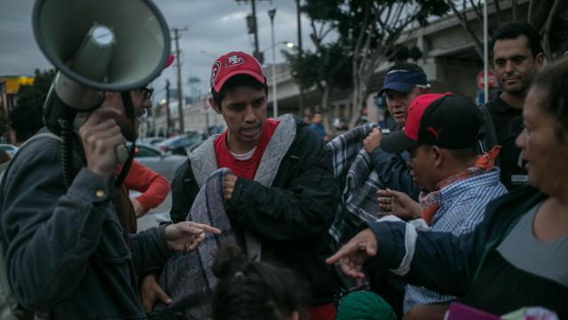 Members of a caravan of migrants from Central America who traveled through Mexico line up for blankets as temperatures drop outside Tijuana's pedestrian west border crossing with the U.S., in Mexico, April 29, 2018. The migrants were told Sunday afternoon that the immigration officials could not process their claims, and they would have to spend the night on the Mexican side of the border. (Meghan Dhaliwal/The New York Times)