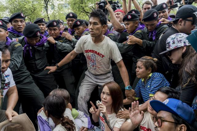 FILE — Pro-democracy activists scuffle with police before being detained during a protest to mark the anniversary of the 2014 coup in Bangkok, May 22, 2018. Assets of the Thai royal family that have been managed by an official agency have been turned over to direct ownership by the king, who will be able to manage them as he sees fit, but must also begin to pay taxes on them, the agency has said. (Adam Dean/The New York Times)