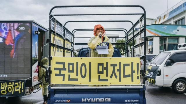 """Lee Hyang moderates the anti-immigrant protest at Jeju City Hall in South Korea, June 30, 2018. The arrival of hundreds of Yemenis has created a wave of opposition, leading to what is considered South Korea's first organized anti-asylum movement. The banner reads, """"Koreans First!"""" (Jun Michael Park/The New York Times)"""