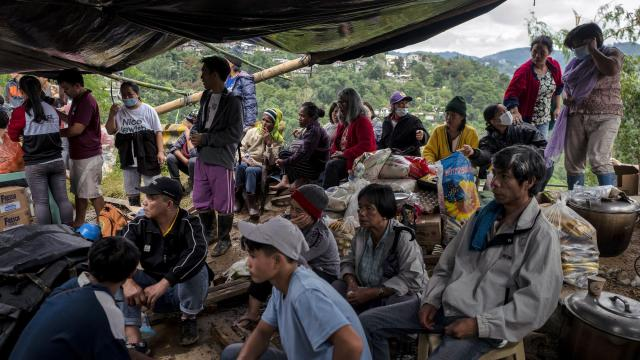Residents and relatives await further news at a staging area near the landslide in Itogon, in the northern Philippines, on Monday, Sept. 17, 2018. Emergency workers recovered 43 bodies from the muddied wreckage of a gold miners' bunkhouse after Typhoon Mangkhut set off a landslide, burying the remote northern town of Itogon in a river of debris and potentially doubling the country's death toll, officials said on Monday. (Jes Aznar/The New York Times)