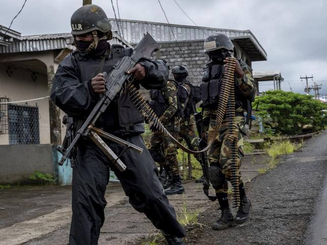 Government soldiers in Ekona, a small town outside of Buea, Cameroon, Oct. 4, 2018. A government crackdown on a separatist movement has been ruthless, emptying cities amid accounts of soldiers burning homes and shooting civilians. Amid the chaos, Cameroon holds an election Sunday. (Ashley Gilbertson/The New York Times)