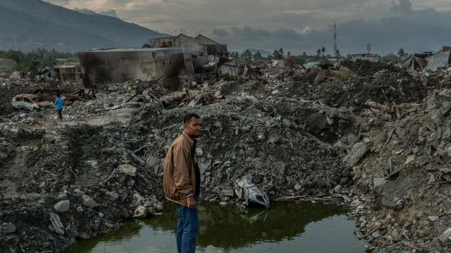 """Anjas Firmansyah looks over where his house used to be after an earthquake and tsunami leveled the area, in Palu, Indonesia, Oct. 11, 2018. Following the destruction, the government has ended the search for bodies, and desperate family members are not ready. """"If God could give me just one,"""" Firmansyah said, """"it would be enough."""" (Ben C. Solomon/The New York Times)"""
