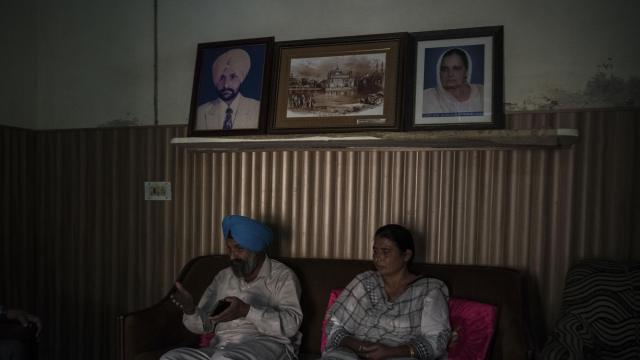 """Harinder Singh, a farmer, and his wife in heir home in Bishanpur Channa, India, Oct. 28, 2018. Singh has adopted technology to clear his agricultural land of stubble rather than burning it, a common practice that has contributed to India's toxic air. """"Our objective is to reduce pollution,"""" he said. (Rebecca Conway/The New York Times)"""