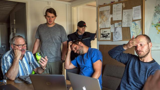 In a handout photo, Thomas Krumpen, seated at center, a sea-ice physicist with the Alfred Wegener Institute, and crew members plan a flight to survey the thickness of ice in the Arctic Ocean, at Station Nord, a Danish military and scientific outpost in Greenland, Aug. 2, 2018. Scientists at Station Nord are monitoring the ice in the Arctic as part of efforts to understand the effects of global warming. (Esther Horvath via The New York Times) -- NO SALES; FOR EDITORIAL USE ONLY WITH NYT STORY SLUGGED GREENLAND ICE OUTPOST BY HENRY FOUNTAIN FOR SEPT. 21, 2018. ALL OTHER USE PROHIBITED.