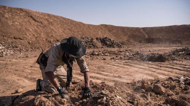 FILE -- An Iraqi army soldier searches for remains at the mass grave that was discovered at a trash dump site on the outskirts of Hammam Al-Alil after it was liberated by Iraqi forces, in Iraq, Nov. 12, 2016. More than 200 mass graves holding as many as 12,000 bodies have been found in areas of Iraq that were once controlled by the Islamic State, the United Nations said. (Sergey Ponomarev/The New York Times)