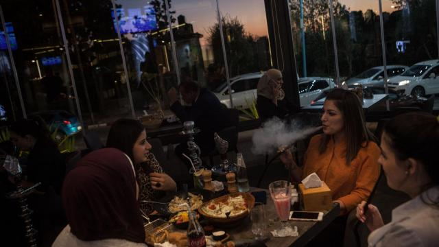 FILE -- Palestinian university students eat and smoke shisha at one of Ramallah's new and busy restaurants, in the West Bank, Sept, 4, 2018. For months, Israel has tried to quell Gaza's border protests through force. Now Israel is taking a different approach, easing a blockade and allowing millions of dollars in aid to flow into Gaza and to Hamas, its bitter foe, which controls the impoverished enclave. (Erin Trieb/The New York Times)
