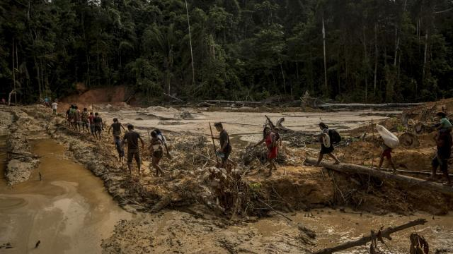 """Members of the indigenous Munduruku tribe cross protected land in Brazil that was destroyed by illegal gold mining, deep in the Amazon rainforest, March 31, 2018. Brazil's new far-right president, Jair Bolsonaro, wants to scale back protections for the Amazon rainforest and its indigenous communities. """"Where there is indigenous land,"""" Bolsonaro has said, """"there is wealth underneath it."""" (Meridith Kohut/The New York Times)."""