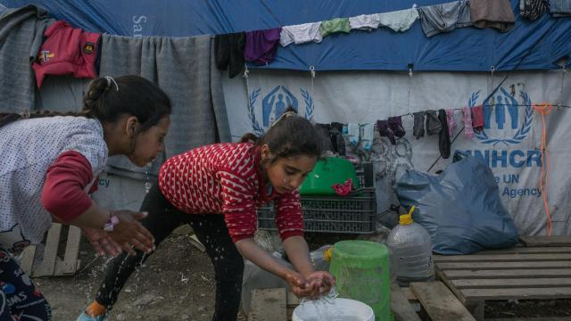 FILE -- Syrian refugee children wash up from a bucket outside their tent in a makeshift camp outside Moria, on the Greek island of Lesbos, March 1, 2018. Centrist leaders in Europe have cut migration to Europe by about 90 percent already, using the kinds of deterrents belatedly recommended by Hillary Clinton. (Mauricio Lima/The New York Times)