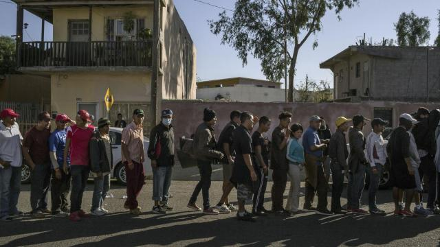 FILE -- Migrants wait to receive food outside a sport center-turned-shelter in Tijuana, Mexico, Nov. 17, 2018. A peaceful march by Central American migrants waiting at the southwestern United States border veered out of control on Nov. 25, 2018, as hundreds of people tried to evade a Mexican police blockade and run toward a giant border crossing into California.(Mauricio Lima/The New York Times)