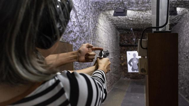 "Instructor helps Natalia Ortega during her shooting practice at Centaurus, a gun training Academy in São Paulo, Nov. 7, 2018. President-elect Jair Bolsonaro wants to make it easier for ""good guys"" to own firearms, though most Brazilians think civilian gun ownership should be banned. (Gabriela Portilho/The New York Times)"