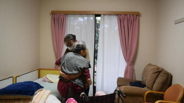 A caregiver moves an elderly resident to a wheelchair in her room at Mother's Garden, a nursing home in Kashiwa, Japan, Dec. 6, 2018. Long seen as one of the most insular of nations, Japan is surprising its neighbors (and perhaps itself) by opening its doors a bit wider to foreign workers. (Noriko Hayashi/The New York Times)