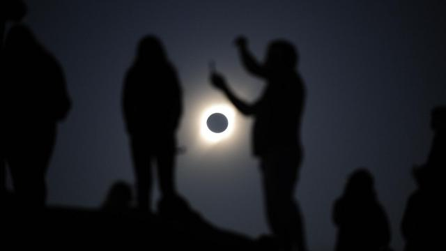 People with protective glasses observe a solar eclipse above La Higuera, Chile, July 2, 2019. Late on Tuesday afternoon, the moon blocked the sun in South America in a total solar eclipse. (Victor Ruiz Caballero/The New York Times)