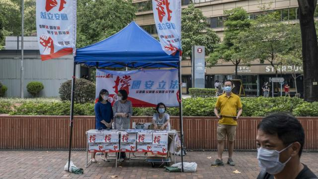 Workers at a booth try to collect signatures in support of the national security law in Hong Kong on Friday, May 29, 2020. China's Communist Party is calculating that control and stability outweigh the benefits that Hong Kong has provided. (Lam Yik Fei/The New York Times)