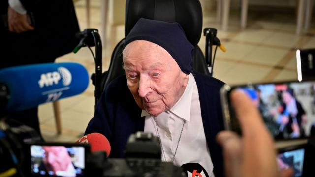 Sister Andre (C), Lucille Randon in the registry of birth, the eldest French citizen, talks with journalists during an event to celebrate her 116th birthday in the EHPAD (Housing Establishment for Dependant Elderly People) in Toulon, southern France, where she has been living since 2009. - Sister Andre was born February 11, 1904. (Photo by GERARD JULIEN / AFP) (Photo by GERARD JULIEN/AFP via Getty Images)