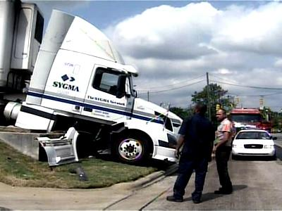 A parked tractor-trailer was left hanging over an embankment Friday morning after it rolled and hit a car.