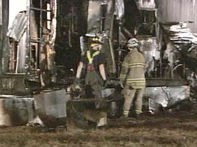 Firefighters inspect the damage to a mobile home outside Chapel Hill after a fire destroyed the residence and killed one person inside.