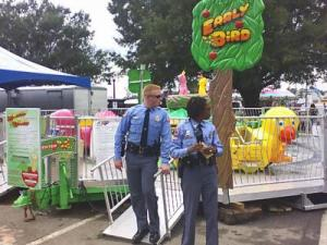 Police officers keep State Fair attendees away from the Early Bird children's ride, which malfunctioned and injured a worker.