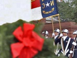 A wreath rests on the headstone of a veteran at Raleigh National Cemetery, while a color guard marches in the background.