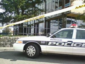 Crime-scene tape surrounds the Durham Police Department Wednesday afternoon while authorities investigate an envelope with a suspicious powder.