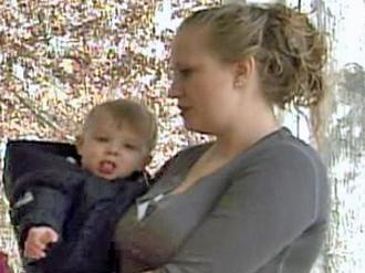 Lauren Massey and her infant son stand on the porch of their new home in Raleigh. A fire killed her fiancee and her family's house in Garner on Sept. 16, 2006.