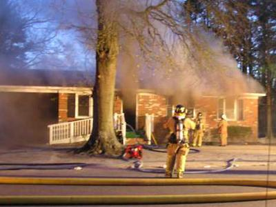 Smoke pours out of a window of a house at 401 W. Barrington St. that caught fire Saturday, March 1, 2008. (Photo courtesy of Robert A. Jordan)