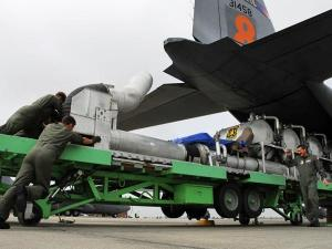 North Carolina Air National Guardsmen load equipment that turns this C-130 cargo plane into an aerial tanker for fighting wildfires.