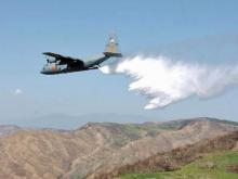 A C-130 equipped with modular tanks and pumps dumps fire retardant out its cargo ramp.
