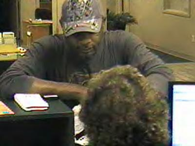 Surveillance cameras caught a bank robber who handed a note to a teller at the Mechanics & Farmers Bank, 13 E. Hargett St. in Raleigh, around 2:30 p.m. on Friday, July 18, 2008.