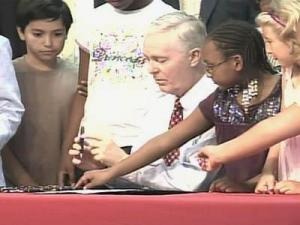 Gov. Mike Easley signs a bill for North Carolina to join the Interstate Compact on Educational Opportunity for Military Children during a ceremony in Fayetteville on Aug. 7, 2008.