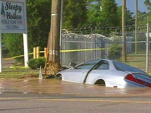 A silver Honda got stuck in a sinkhole on Murchinson Road early Saturday, Sept. 27, 2008. A toppled fire hydrant was also in the sinkhole, spewing water.