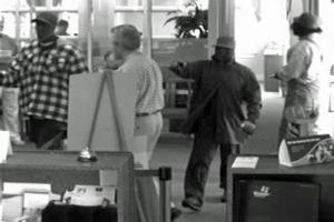 In the surveillance photo, the suspects are the individuals seen on the left, the right and the second from the right. The fourth individual in the photo (second from the left) is not a suspect.