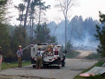 Firefighters battle a blaze in a wooded area across from the Hunters Way subdivision at the 800 block of Lee Road in Clayton on April 18, 2009. (Submitted by Jeff Godwin)