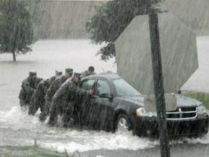 Eight Army National Guard soldiers, including four from North Carolina, on a recreational run stopped to help a mother and daughter trapped in a flooding parking lot in Hattiesburg, Miss., Saturday, May 16, 2009. They helped the women get to safety and then pushed the stranded car out of the flooded parking lot. (Photo by Claude Dixon, 46th Military History Detachment)