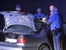 Law enforcement agents search a car whose driver led them on an hour-long chase through Wake and Chatham counties early Monday, June 8, 2009. At least one person in the car was a suspect in shootings earlier that night.