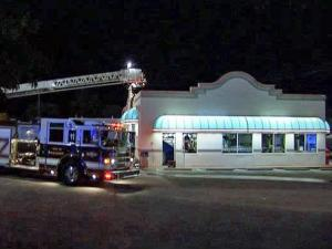 Firefighters use a ladder truck to put out a fire at Miami Subs, 3701 New Bern Ave., around midnight Thursday, July 2, 2009. Fire investigators believe the flourescent lighting surrounding the roof somehow caused two fires in the past two weeks. Damage was mostly contained to the roof.